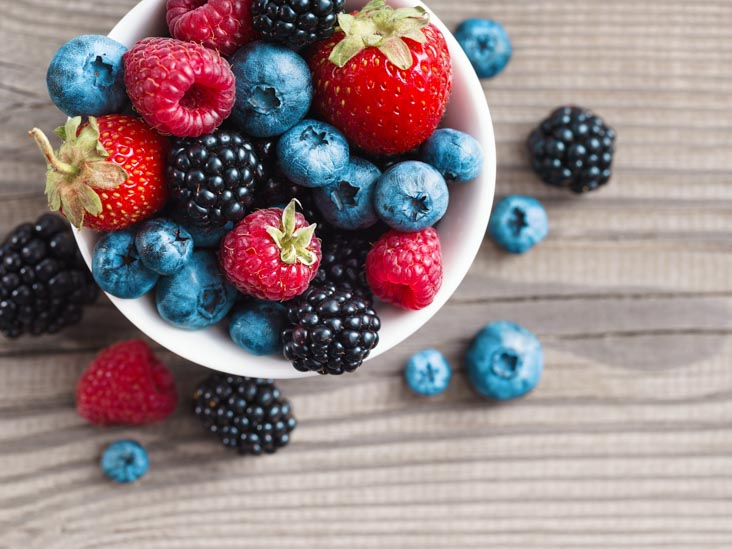 Fresh berries in a basket on rustic wooden background.